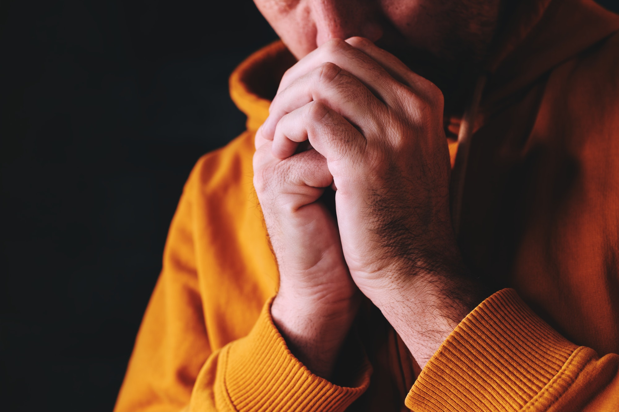 Christian man praying to God in dark room with clasped hands