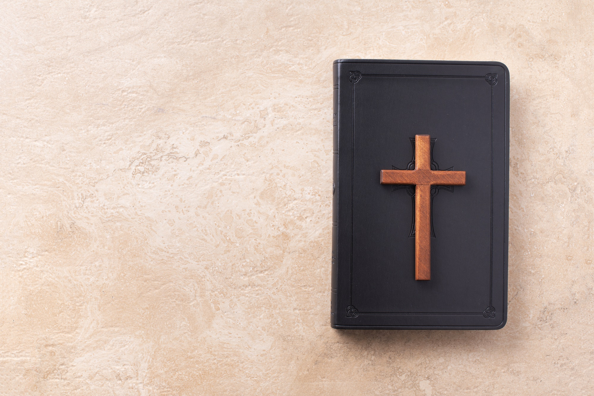 Wooden cross on Bible over marble background. Reminder of Jesus sacrifice and Christ resurrection