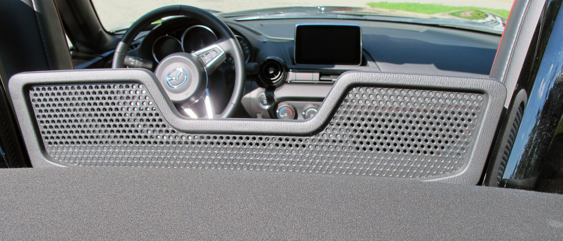 The soft top on the MX-5 is easily raised and lowered by one hand and features a glass rear window with defroster and includes a draft blocker between the seats.