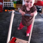 "Fia has begun to pick herself up and walk with her ""block-cart"". We're in trouble soon!"