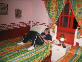 A young participant lounges in a brightly colored hotel room.