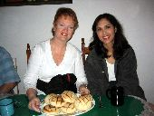 Two women holding a tray of sweet buns in restaurant in Batopilas.