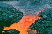 Orange lava flows over rocks at Volcanoes National Park.