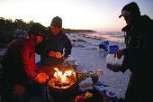 The participants prepare breakfast on the beach as the sun rises over the Gulf of Mexico.