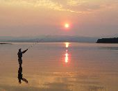 A participant fishes on Yellowstone Lake as the the sun rises.