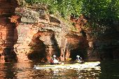A tandem sea kayak travels past a set of sea caves on Lake Superior.