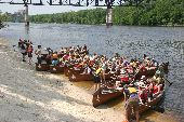 Nine full voyageur canoes set off from the sandy shores of East River Flats for a day on the water.