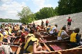 On a sandy shore of the Mississippi, voyageur canoes full of participants get a history lesson from National Park Service rangers.