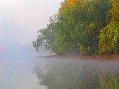 Fog hangs over the river and clings to the trees on the shores of the Mississippi River on an early autumn morning.