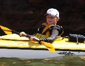 A young boy in the bow of a tandem sea kayak enjoys paddling to Sand Island on a sunny day in the Apostle Islands.
