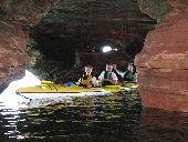 A family in a sea kayak explores the inside of one of the caves at Sand Island.