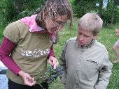 A trip leader teaches a participant about nature by pointing out the details of a pine cone.