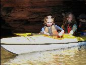 Two young girls emerge from an Apostle Islands sea cave in their kayak.