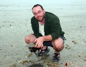 Trip leader Robb holds a large horseshoe crab on a beach in the Gulf of Mexico.