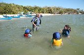 Trip leader and three kids swim in the warm waters off the coast of Florida.