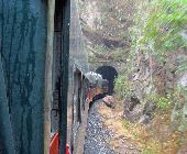 A train enters a tunnel through a mountainside in Mexico.