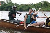 Josh, Patti, and Rosie paddle on the Mississippi River at the stern of a voyageur canoe.