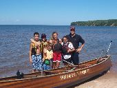Participants stand on the beach in front of their voyageur canoe, preparing to paddle to Mawikwe Bay.