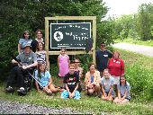 A group of participants poses in front of the welcome sign at Wilderness Inquiry's Apostle Islands base camp.