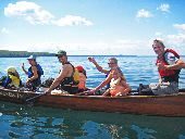 A family waves from their voyageur canoe as they paddle to Sand Island.