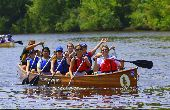 Group on a river paddles a Voyageur canoe; one participant waves at the camera.
