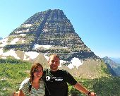 A man and woman pose for a picture with an incredible, mountainous background.