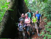 Six participants pause on a trail in Costa Rica next to a large tree.