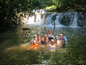 Group in swimming below a waterfall in the jungle.