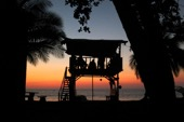 A silhouette of a clubhouse against an evening sunset in Costa Rica.