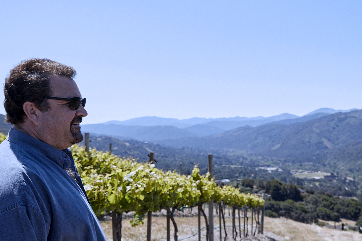 """Winemaker David Coventry surveys the Salinas Valley in front of some of the many acres of hillside vines."""