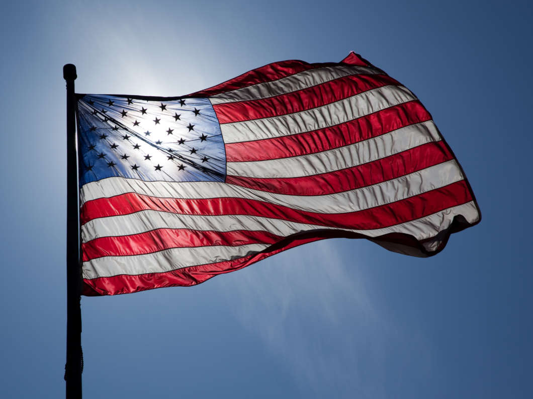 US Flag, backlit by the sun, waves on a windy day in NYC. Photo by Flickr user jnn1774; creative commons
