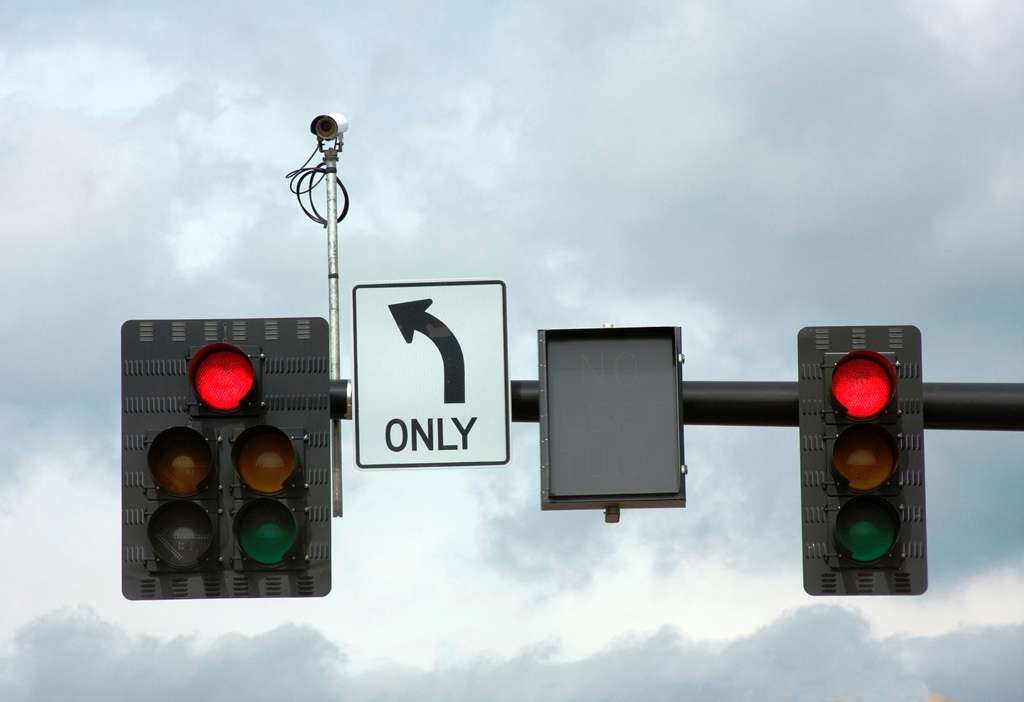 Traffic Signals and Camera Against a Cloudy Sky