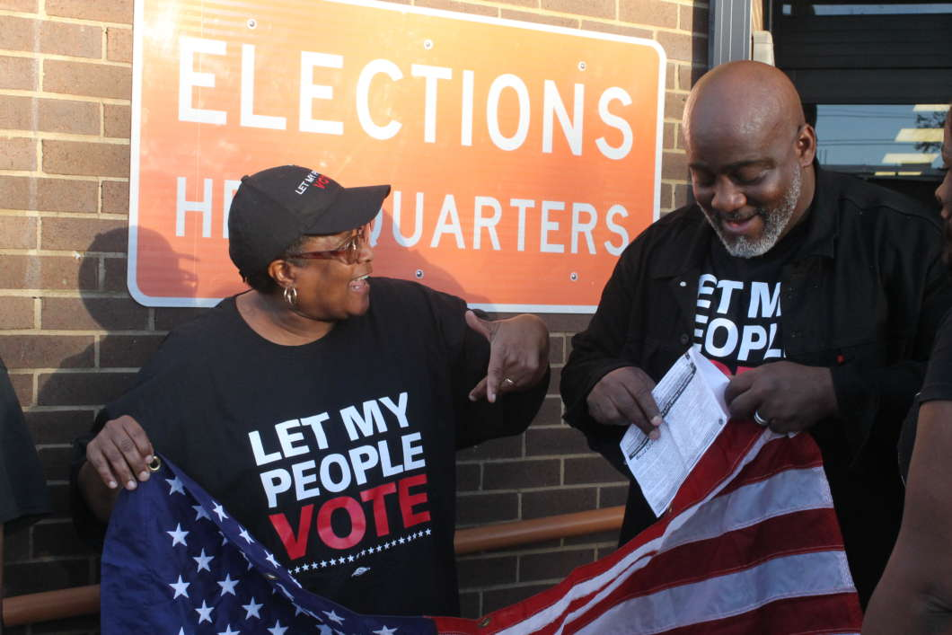 Desmond Meade (r) shows off his voter registration slip outside the Orange County Supervisor of Elections office. Photo: Emily Lang, WMFE