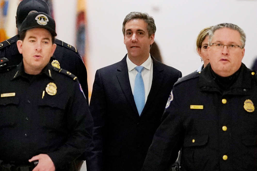Michael Cohen, the former personal attorney of President Trump, is escorted by Capitol Hill police officers as he arrives to testify at a House Committee on Oversight and Reform hearing on Wednesday