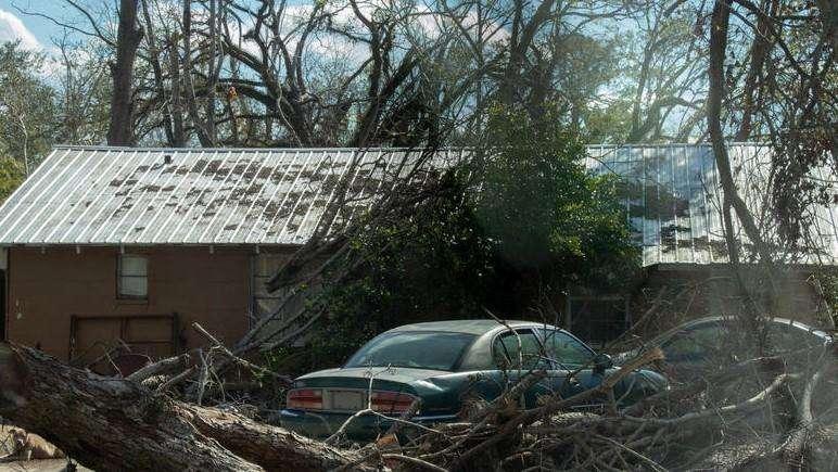 A fallen tree lies in front of a house in Marianna, FL. Photo: SHAWN MULCAHY / WFSU