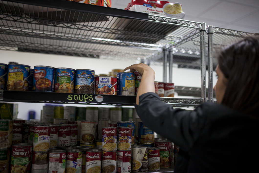 A volunteer stocking shelves with canned food at a University of Florida food pantry. Photo courtesy the university
