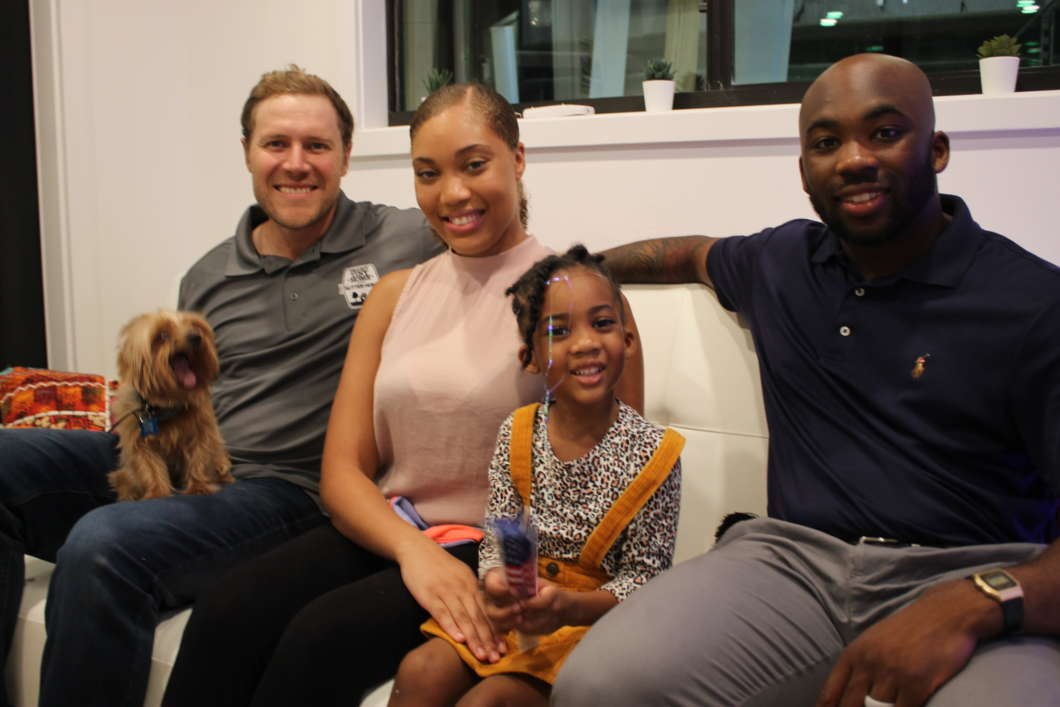 (Left to right) Co-Host Zach Giffin, Shanice Iniss, Kevin Iniss, and their daughter. Kevin and Shanice Iniss and their young daughter share a seat inside their new home which will be featured on Tiny House Nation. Photos by Jason Delgado for WMFE.