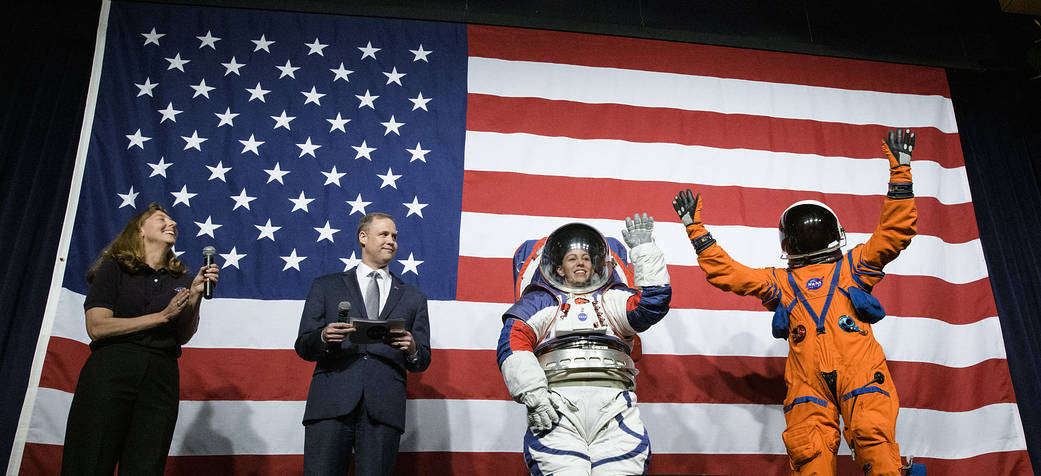 Amy Ross, a spacesuit engineer at NASA's Johnson Space Center, left, and NASA Administrator Jim Bridenstine, second from left, watch as Kristine Davis, a spacesuit engineer at NASA's Johnson Space Center, wearing a ground prototype of NASA's new Exploration Extravehicular Mobility Unit (xEMU), and Dustin Gohmert, Orion Crew Survival Systems Project Manager at NASA's Johnson Space Center, wearing the Orion Crew Survival System suit, right. Photo Credit: (NASA/Joel Kowsky)