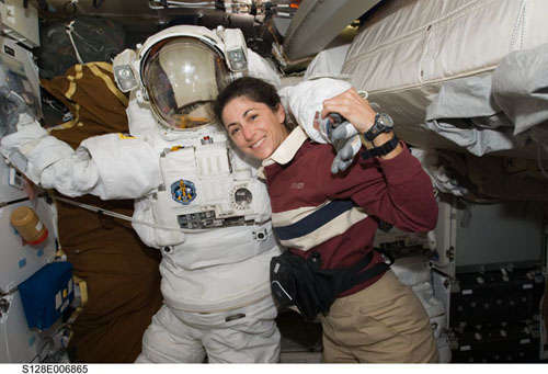 Astronaut Nicole Stott poses with an EVA suit on the International Space Station. Photo: NASA