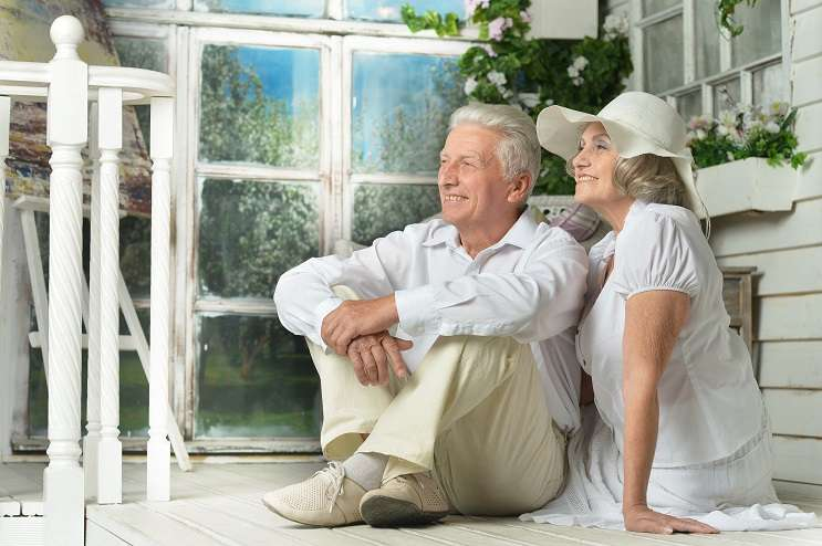 Portrait of beautiful elderly couple on wooden porch