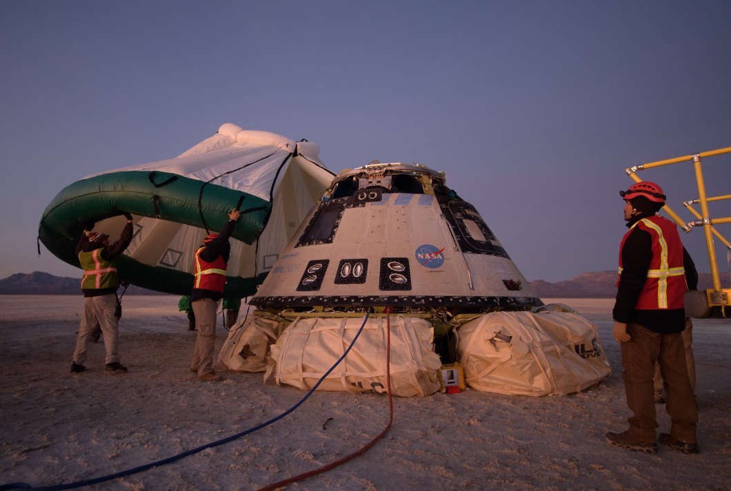 Boeing, NASA, and U.S. Army personnel work around the Boeing CST-100 Starliner spacecraft shortly after it landed in White Sands, New Mexico, Sunday, Dec. 22, 2019. The landing completes an abbreviated Orbital Flight Test for the company that still meets several mission objectives for NASA's Commercial Crew program. The Starliner spacecraft launched on a United Launch Alliance Atlas V rocket at 6:36 a.m. Friday, Dec. 20 from Space Launch Complex 41 at Cape Canaveral Air Force Station in Florida. Photo Credit: (NASA/Bill Ingalls)