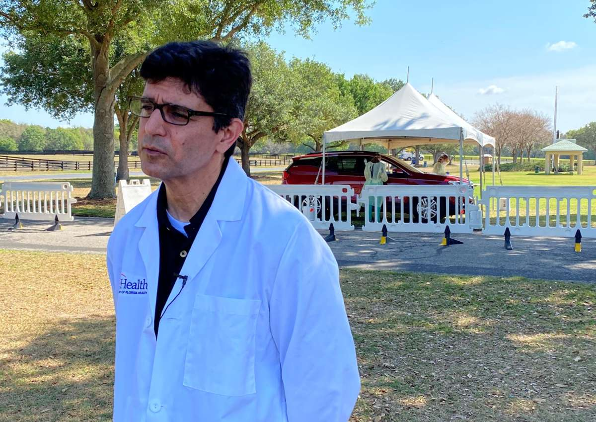 Dr. Michael Lauzardo, an expert on infectious disease and global medicine, speaks to the media as drive-thru testing takes place behind him in The Villages on Monday. Photo: Joe Byrnes