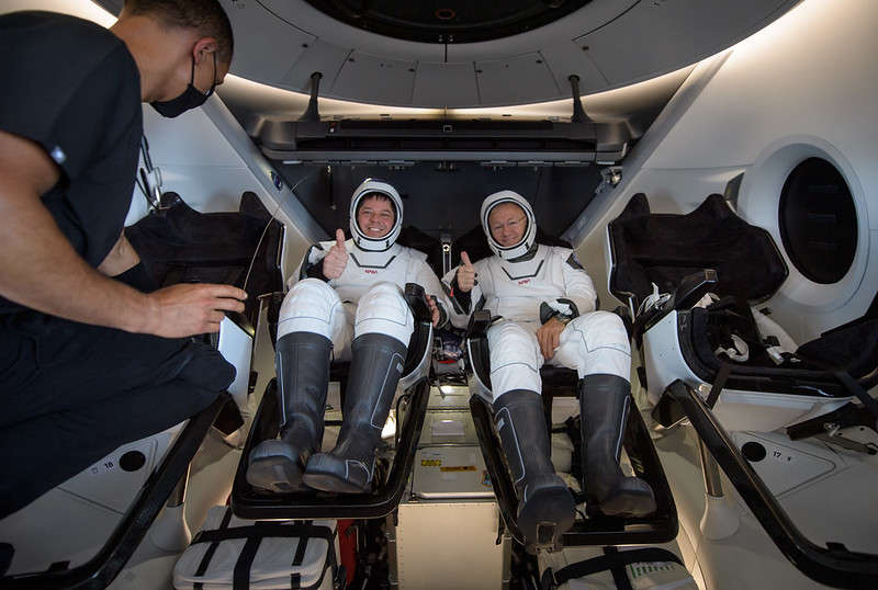 NASA astronauts Robert Behnken, left, and Douglas Hurley are seen inside the SpaceX Crew Dragon Endeavour spacecraft onboard the SpaceX GO Navigator recovery ship shortly after having landed in the Gulf of Mexico off the coast of Pensacola, Florida, Sunday, Aug. 2, 2020. The Demo-2 test flight for NASA's Commercial Crew Program was the first to deliver astronauts to the International Space Station and return them safely to Earth onboard a commercially built and operated spacecraft. Behnken and Hurley returned after spending 64 days in space. Photo Credit: (NASA/Bill Ingalls)