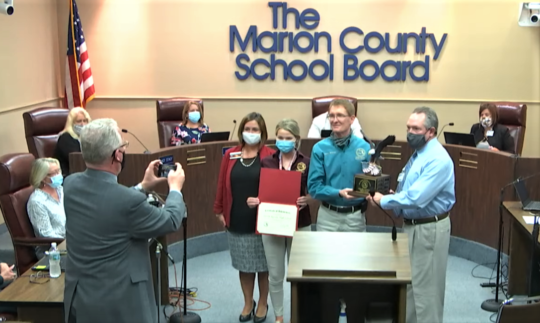 Supervisor of Elections Wesley Wilcox, second from right, presents a trophy to North Marion High School U.S. government teacher Michael Hill Tuesday night. Image: MCPS via video
