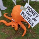 Money in politics sign held by an orange octopus!