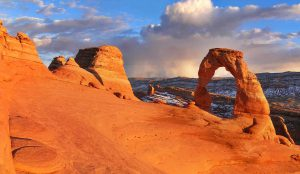 The arches in Utah with clouds in the distance