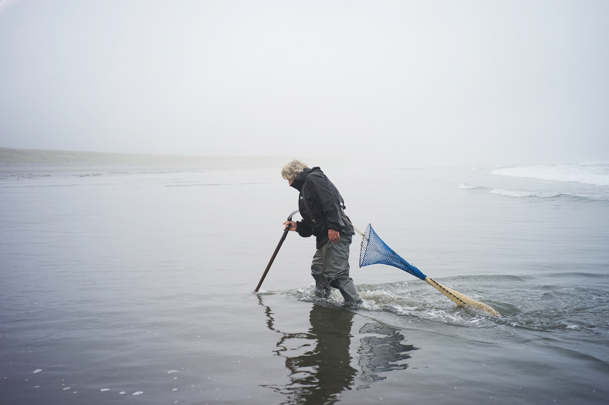 Richard Darbonne photographs Ron Neva trudging through the water hunting for razor clams for 1859 magazine