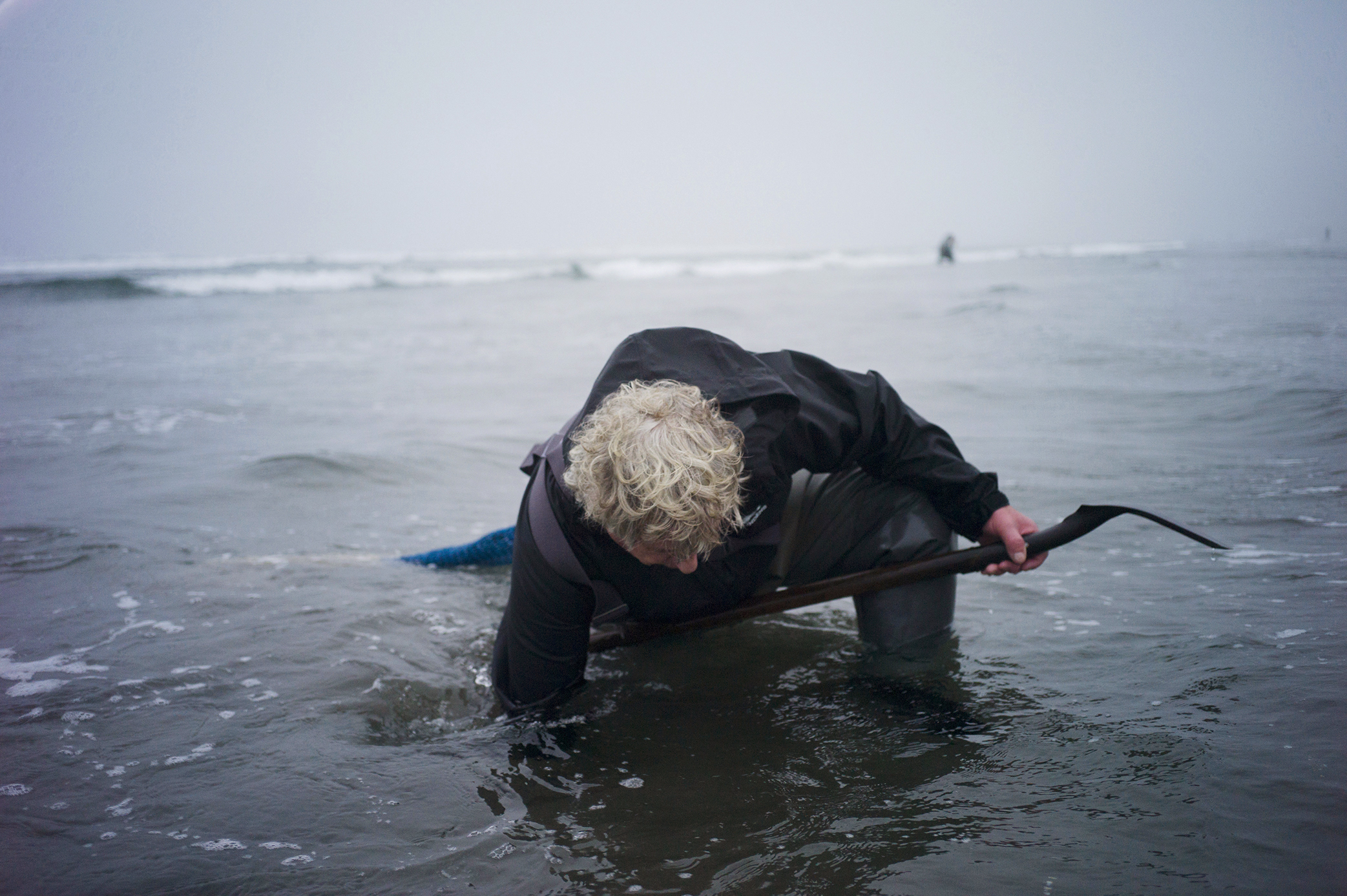 Richard Darbonne photographs Ron Neva as he reaches down into the water in hopes of finding a razor clam for 1859 Magazine