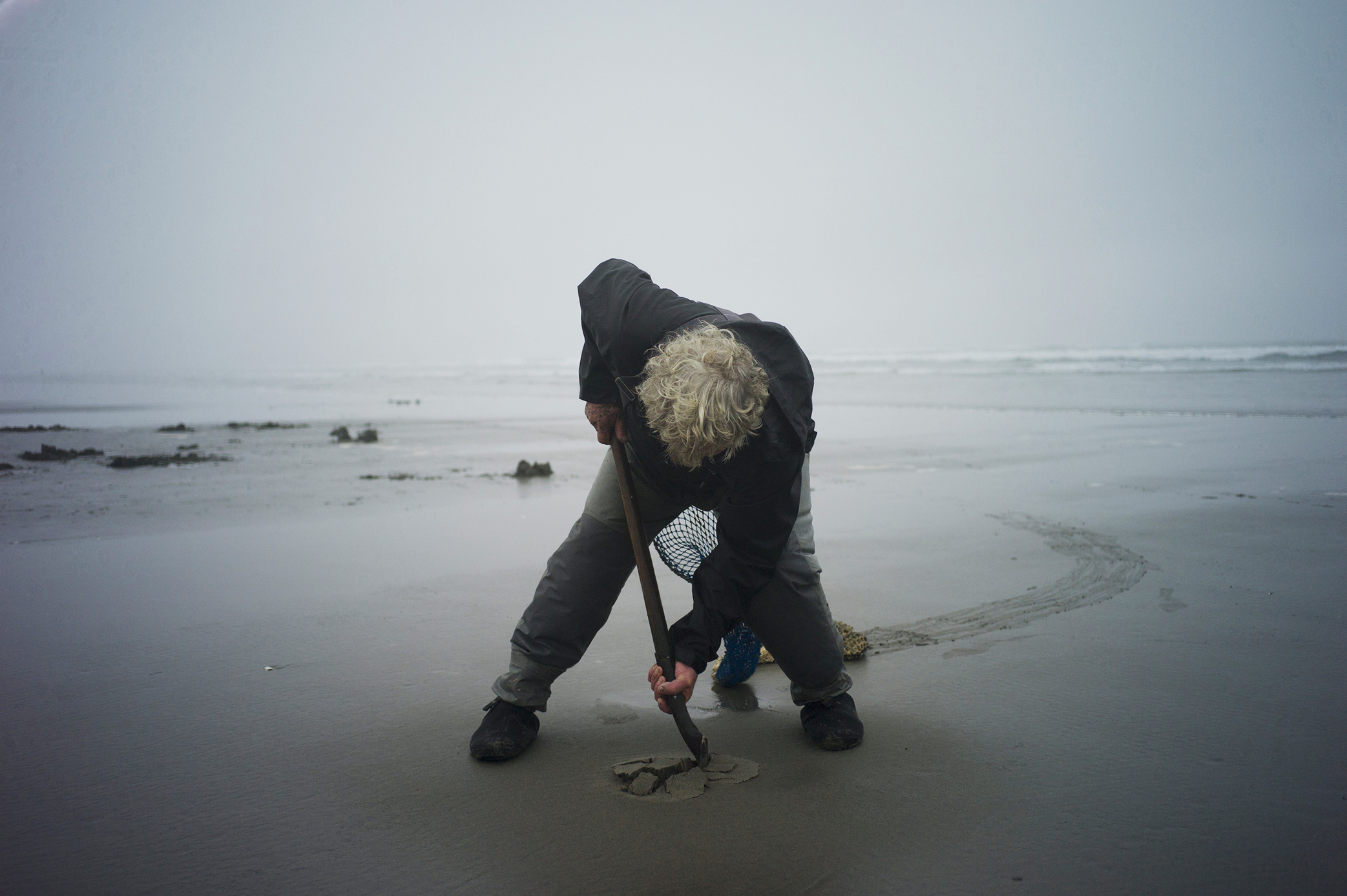 Richard Darbonne captures clam harvester Ron Neva sticking his small shovel deep into the sand for 1859 magazine