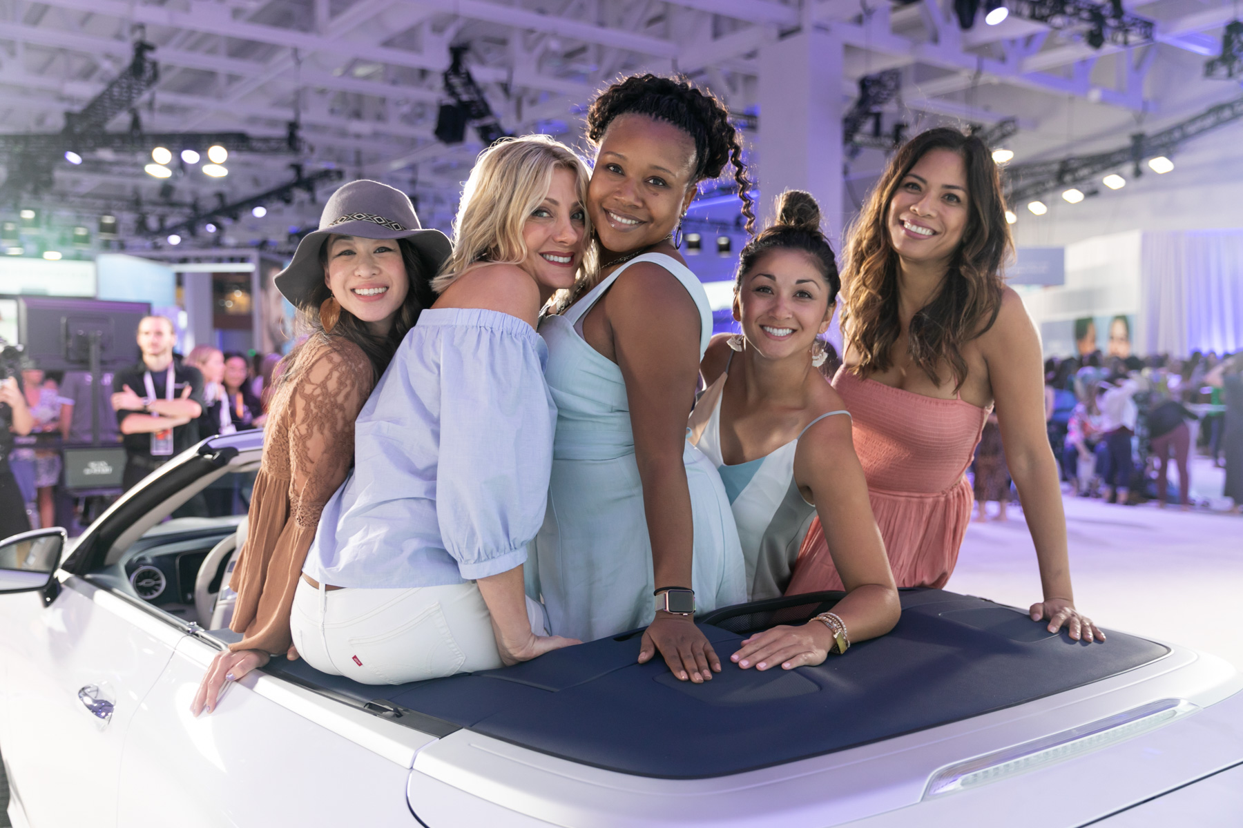 Five young women dressed in pastels sitting on the back of a convertible on a trade show floor captured by Margo Moritz